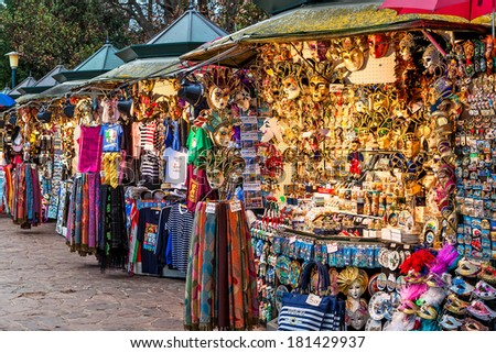 VENICE, ITALY - NOVEMBER 13, 2012: Vendors stands - profitable and popular form of sales traditional souvenirs and gifts like masks, magnets, clothes and travel guides to tourists visiting Venice. - stock photo