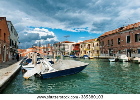 VENICE, ITALY - 17 OCTOBER 2015: Boats moored in a canal, Murano, Venice, Italy on the lagoon island of Murano known for its historic glass manufacturing - stock photo