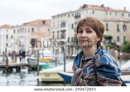 VENICE, ITALY - on MAY 1, 2015. The happy tourist is photographed against the Grand Channel (Canal Grande)  - stock photo