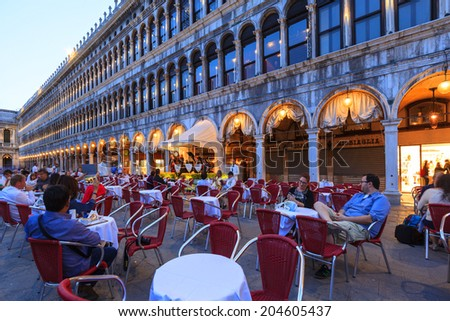 VENICE - JUN 2:People in the restaurant in St Mark's Square, Venice Italy. Each year the city receives 20 million tourists. This equates to approximately 60,000 visitors each day  2014 Italy - stock photo