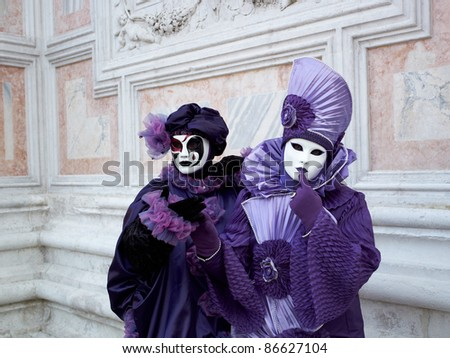 VENICE - MARCH 5: Couple in Venetian costume attend the Carnival of Venice, annual festival starting two weeks before Ash Wednesday and ends on Shrove Tuesday, on March 5, 2011 in Venice, Italy. - stock photo