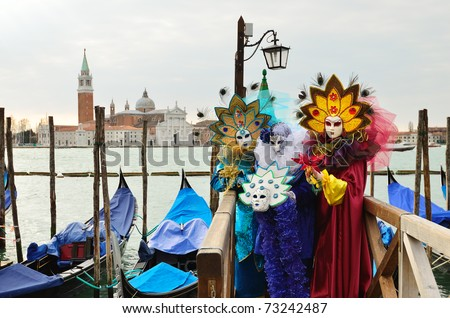 VENICE - MARCH 7: Three unidentified masked persons in costume in St. Mark's Square during the Carnival of Venice on March 7, 2011 in Venice. The 2011 carnival was held from February 26th to March 8th - stock photo
