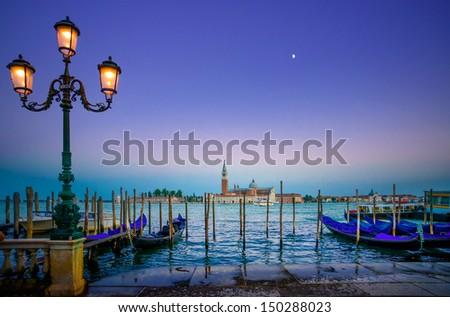 Venice, street lamp and gondolas or gondole on a blue sunset twilight and San Giorgio Maggiore church landmark on background. Italy, Europe. - stock photo