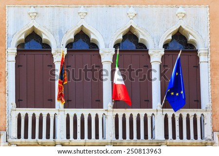 Venice  the Pearl of Italy. Balcony of the old building with the flags of Venice, Italy, and the European Union.  - stock photo