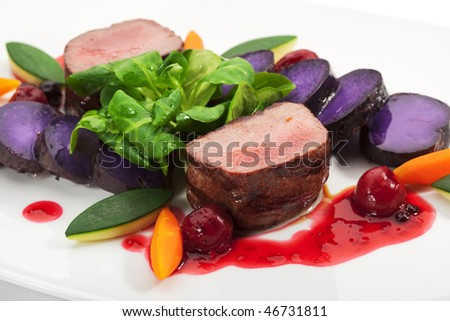 Venison Meat with Carrots, Zucchini, Herbs and Blue Potato. With Sauce and Red Berries - stock photo