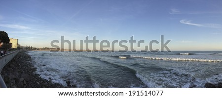 VENTURA, CA - APRIL 23, 2014: Walking people and surfers enjoying cool Pacific ocean breeze and waves near historic wooden pier, City of San Buenaventura, Southern California - stock photo