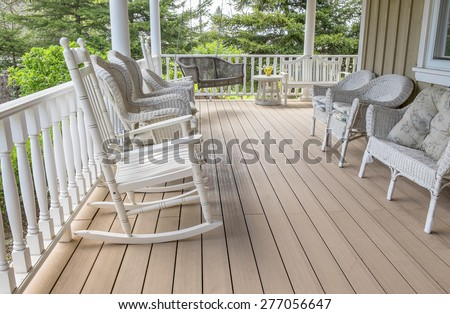 Veranda Filled With White Wicker Chairs, With a Rocking Chair in the Foreground - stock photo