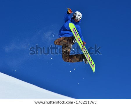 VERBIER, SWITZERLAND - FEBRUARY 21: Freestyle snowboarder performing rear grab stunt and trailing snow:  February 21, 2014 in Verbier, Switzerland  - stock photo