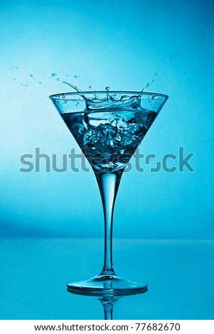Vermouth cocktail inside martini glass over blue background - stock photo