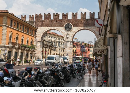 VERONA, ITALY - JULY 18, 2013: Busy street in Verona with Portoni della Bra, medieval gate leading to the Piazza Bra in historic city center. Pedestrians and traffic visible.  - stock photo