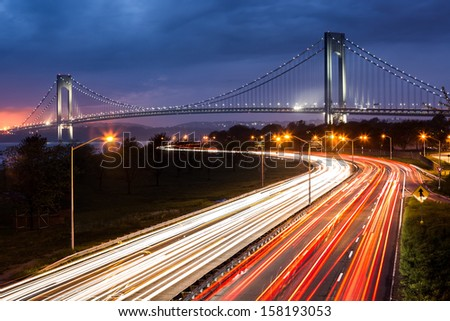 Verrazano Narrows Bridge above the light trails of the Belt Parkway traffic. - stock photo
