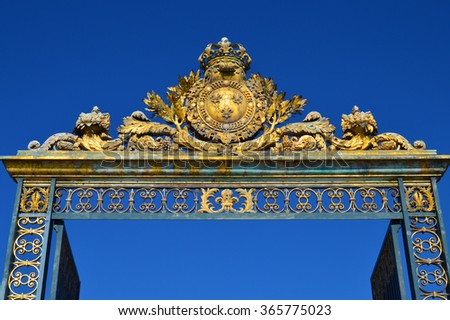 VERSAILLES, FRANCE - April 19, 2015:  Golden Main Gates of the Versailles Palace. The Palace Versailles was a royal chateau. It was added to the UNESCO list of World Heritage Sites. Paris, France. - stock photo