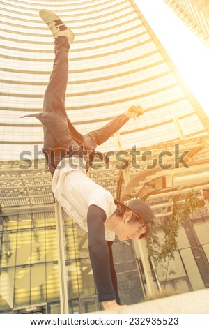 vertical action move in business center. young boy performing parkour moves. - stock photo