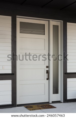 Vertical Angled Shot of White And Black Front Entryway with White Siding, a White Front Door, and Black Framing - stock photo