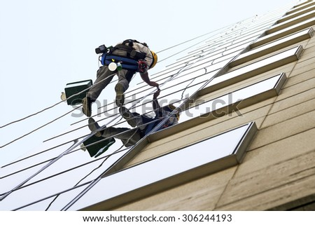 vertical climber worker hanging on ropes to cleaning the windows of a modern building - stock photo