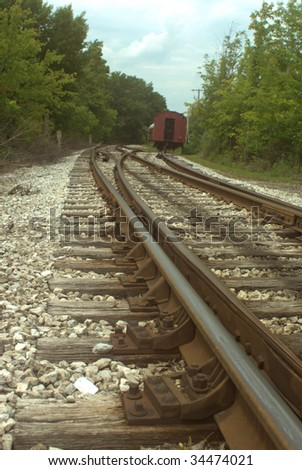 vertical close-up of railroad tracks with old box cars - stock photo