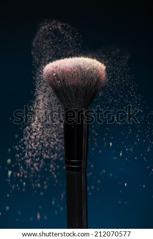 Vertical close-up photo of professional   black make-up brush with pink powder in motion isolated on blue background  - stock photo