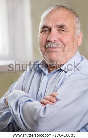 Vertical close-up portrait of a Caucasian senior man with mustache and folded arms, wearing a light grey shirt while smiling at camera - stock photo
