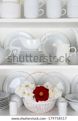 Vertical closeup of a  basket of roses on the shelf of a cupboard full of white plates. Items include, plates, saucers, bowls and a gravy boat. There is one red rose amongst all the white. - stock photo