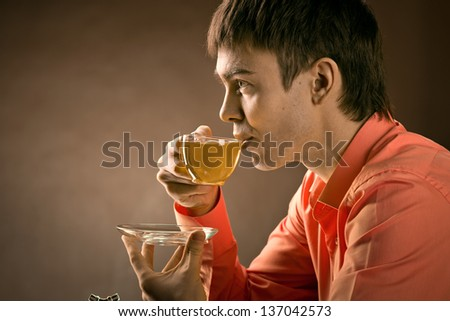 vertical closeup portrait  the  beautiful man hold cup with green  tea,  on brown background - stock photo