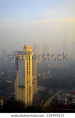Vertical color capture of Bombay skyline, view osbcured by the city haze and smog in the early hours of the day as the sun rises casting a golden hue over the tall buildings - stock photo