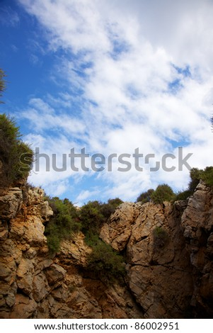 Vertical color image of a sky view from inside an open cave in the ground. - stock photo