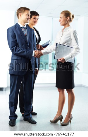 Vertical full-length shot of business people shaking hands with a smile - stock photo