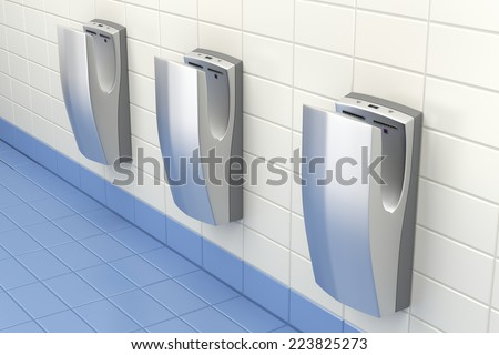 Vertical high speed hand dryers in public washroom - stock photo