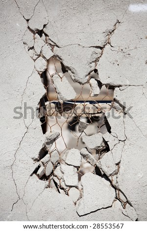 Vertical image of a broken wall showing the studs and chicken wire. - stock photo