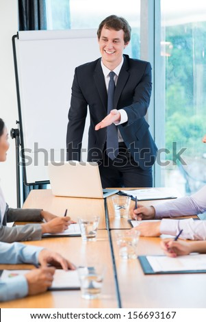 Vertical image of a business ceo addressing to his colleagues while explaining the strategy of the company on the foreground - stock photo