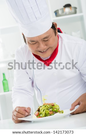 Vertical image of a chef cook with a tasty dish on the table inside - stock photo