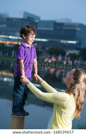 Vertical image of a happy mother having fun with her son on the foreground outside   - stock photo