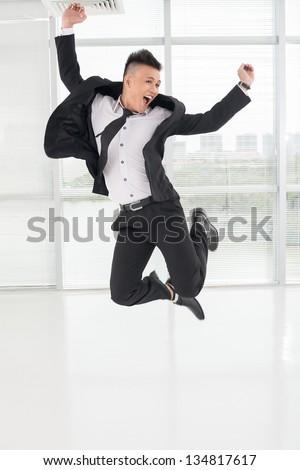 Vertical image of a jumping young asian businessman - stock photo