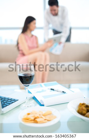 Vertical image of a table with lunch of modern businesspeople on the foreground - stock photo