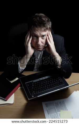 Vertical image of a tired business man working late into the night with black background  - stock photo