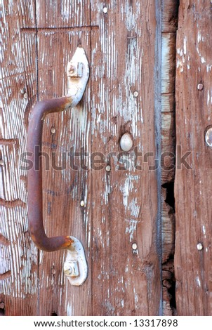 Vertical image of a worn and weathered metal handle with most of the paint worn off against an old, weathered and worn barn door. - stock photo