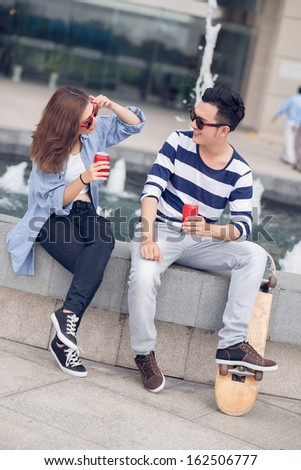 Vertical image of a young couple drinking cola and having fun together outside - stock photo