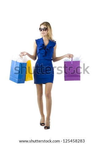 Vertical image of a young female model in blue dress wearing shades while holding shopping bags on both hands - stock photo