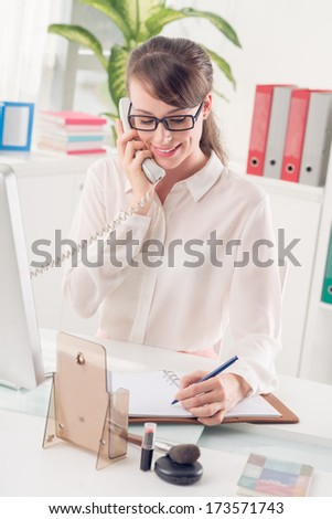 Vertical image of a young secretary making notes while consulting somebody on the phone at the office  - stock photo