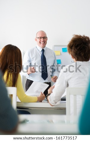 Vertical image of an enthusiastic teacher having a seminar at college - stock photo