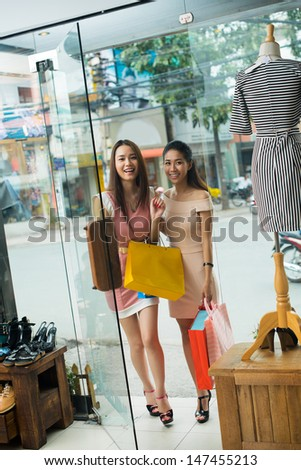 Vertical image of attractive girlfriends on shop entering  - stock photo