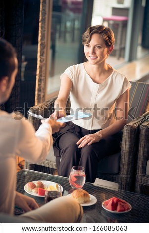 Vertical image of business partners dealing at a cafe during their lunch - stock photo