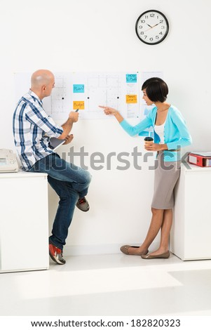 Vertical image of business partners working out strategy of company together - stock photo
