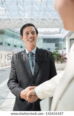 Vertical image of businesspeople handshaking inside - stock photo