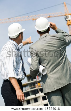 Vertical image of foremen interacting together at meeting - stock photo