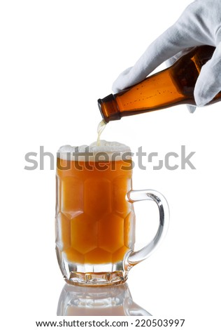 Vertical image of gloved hand pouring amber color beer into glass stein on white with reflection  - stock photo