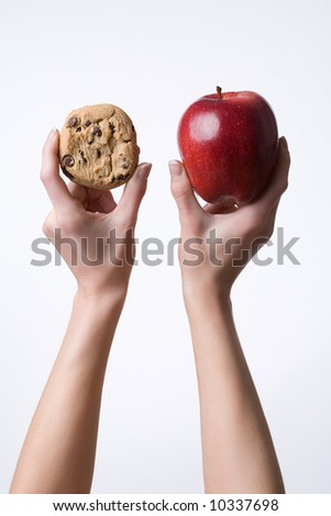 Vertical image of hands holding up a cookie and apple before a white background - stock photo