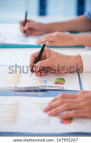 Vertical image of human hands analyzing graphs on the business seminar - stock photo