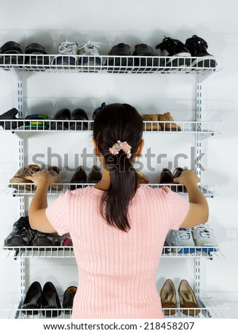 Vertical image of mature woman, back towards camera, deciding which shoes to select from shoe rack  - stock photo