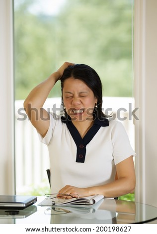 Vertical image of mature woman showing extreme stress while working from home with bright daylight coming in from window in background - stock photo